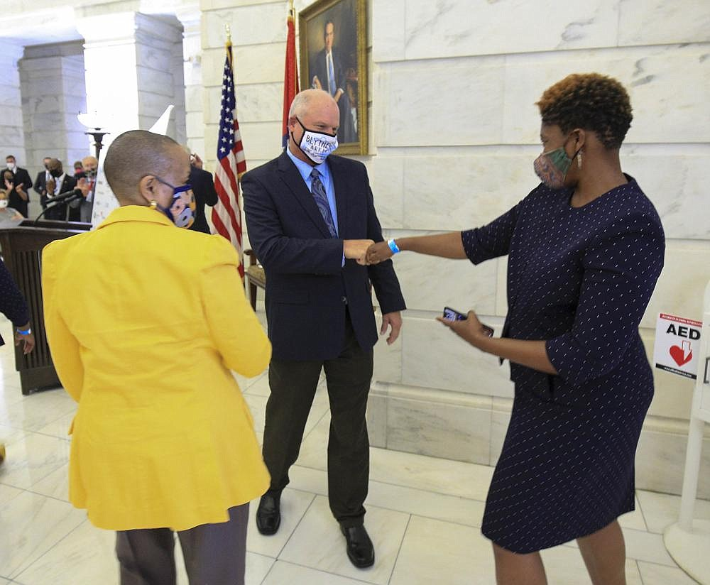 Sen. Jim Hendren, R-Gravette, fist bumps Rep. Denise Ennett as he talks with her and Sen. Joyce Elliott, both Little Rock Democrats, at the Capitol after a Wednesday news conference to reveal a draft of a proposed hate-crime bill to be considered during next year's legislative session. More photos at arkansasonline.com/820leg/.