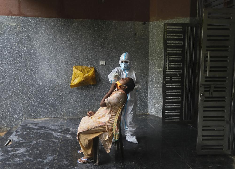 A health worker conducts a coronavirus test Thursday at a government school in New Delhi, India. The country has the fourth-most covid-19 deaths in the world and the third-most cases, with over 2.7 million. (AP/Manish Swarup)