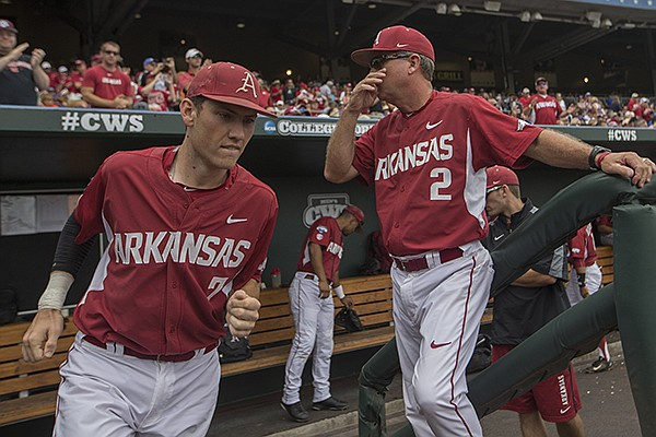 Arkansas third baseman Bobby Wernes (left) takes the field as head coach Dave Van Horn stands in the dugout prior to a College World Series game against Virginia on Saturday, June 13, 2015, at TD Ameritrade Park in Omaha, Neb.