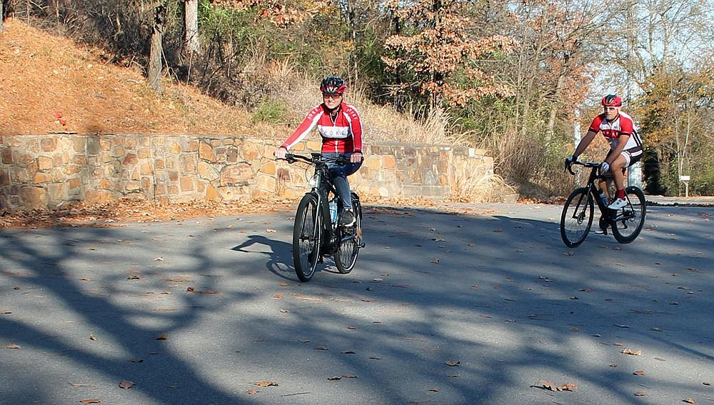 Regina Seelinger (left) and her husband Mat ride e-bikes up a steep hill in North Little Rock in this December 2018 photo; most riders report liking the bicycles' pedal-assist capabilities.