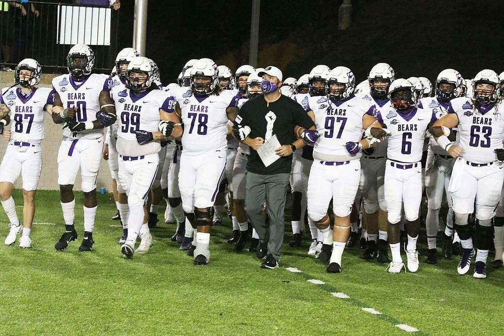 Coach Nathan Brown (middle) walks with his team locked arm-in-arm onto the field Saturday before the Bears' game against Austin Peay at the Cramton Bowl in Montgomery, Ala. (Photo courtesy University of Central Arkansas)