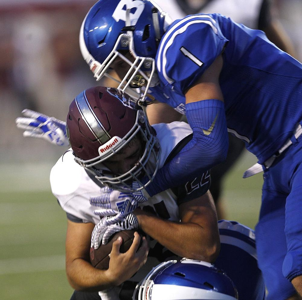 Bryant defender Austin Schroeder (top) tackles Benton running back Cain Simmons for a loss during the first quarter Saturday. (Arkansas Democrat-Gazette/Thomas Metthe)