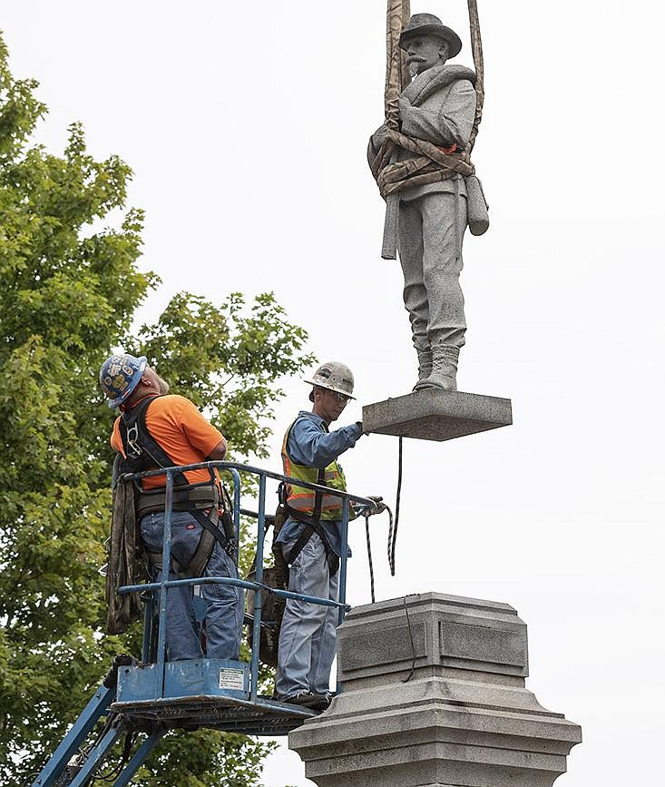 The statue of a Confederate soldier is lifted from its base Wednesday as workers from Nabholz Construction remove it from the Bentonville square. More photos at arkansasonline.com/93removal/. (NWA Democrat-Gazette/Spencer Tirey)