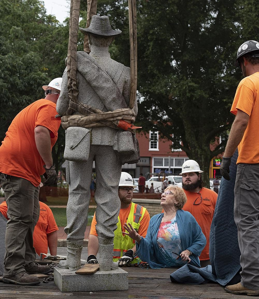 Ann Rossie, with the Arkansas Division of the United Daughters of the Confederacy, checks on the statue of a Confederate soldier after workers from Nabholz Construction removed it from the Bentonville square Wednesday. The Daughters of the Confederacy worked with the Benton County Historical Society and other community members to move the monument to James H. Berry Park, a private park adjacent to the Bentonville Cemetery, where Berry, a former U.S. senator and the 14th governor of Arkansas, is buried. (NWA Democrat-Gazette/Spencer Tirey)