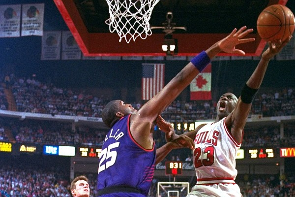Michael Jordan of the Chicago Bulls shoots under pressure from Phoenix Suns Oliver Miller (25) in the second quarter of Game 4 of the NBA Finals, Wednesday, June 16, 1993. Jordan scored 55 as the Bulls defeated the Suns. (AP Photo/John Swart)