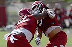 Arkansas defensive linemen Jonathan Marshall (left) and Isaiah Nichols work through a drill Wednesday, Aug. 19, 2020, during practice at the university practice field in Fayetteville.