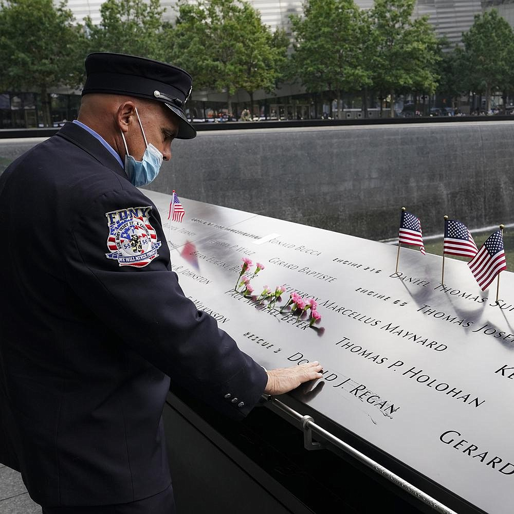 A firefighter mourns over the inscribed names of the victims Friday at the National September 11 Memorial and Museum in New York. Around the country, some communities canceled remembrances because of the pandemic, while others went ahead. More photos at arkansasonline.com/912ceremonies/. (AP/John Minchillo)