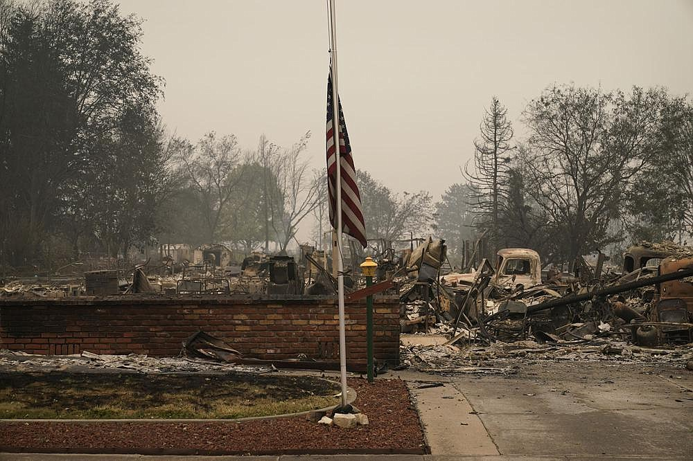 A flag flies Friday over a neighborhood in Phoenix, Ore., that was destroyed along with much of the town when a wind-driven wildfire burned through the area near the California state line. (AP/John Locher)