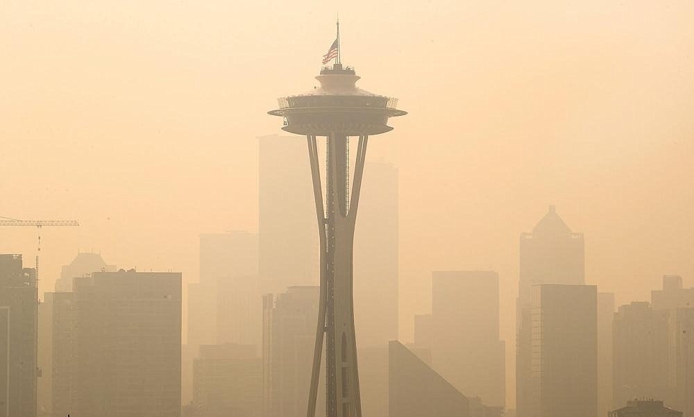 Wildfire-tinted sky (right photo) frames an American flag atop the Space Needle that was lowered to half-staff by the Seattle Fire Department to remember those who lost their lives on Sept. 11, 2001. (AP/The Seattle Times/Mike Siegel)