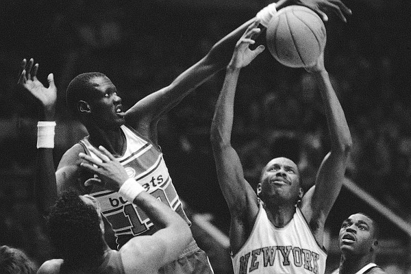 New York Knickerbockers Darrell Walker (4) gets the ball away from Washington Bullets Manute Bol (10) during game at New York's Madison Square Garden on Thursday, Jan. 3, 1986. Knicks Gerald Wilkins (21), right, and Ernie Grunfeld (18), left, and Bullets Cliff Robinson (4), center, watch the action. The Bullets beat the Knicks 115-109. (AP Photo/Richard Drew)
