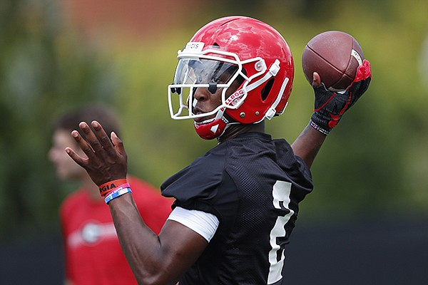 Georgia quarterback D'Wan Mathis throw a pass during the team's first scheduled NCAA college football practice Friday, Aug. 2, 2019, in Athens, Ga. (AP Photo/John Bazemore)