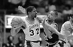 "Los Angeles Lakers guard Earvin ""Magic"" Johnson (32) attempts to pass the ball as San Antonio Spurs guard Alvin Robertson (21) tries to hinder the move during early NBA playoff action, Saturday, April 19, 1986, in Inglewood, Calif. (AP Photo/Michael Tweed)"