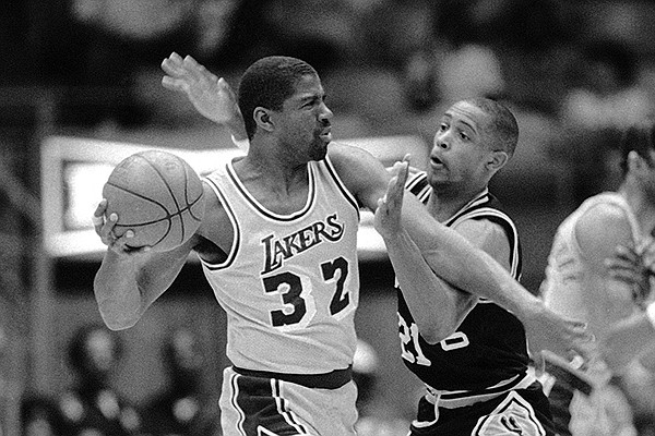 """Los Angeles Lakers guard Earvin """"Magic"""" Johnson (32) attempts to pass the ball as San Antonio Spurs guard Alvin Robertson (21) tries to hinder the move during early NBA playoff action, Saturday, April 19, 1986, in Inglewood, Calif. (AP Photo/Michael Tweed)"""