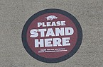 A placard is shown Thursday, Sept. 17, 2020. on the ground at Donald W. Reynolds Razorback Stadium in Fayetteville. The University of Arkansas has added signage across its football stadium to help fans maintain distance this season.