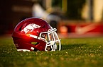 An Arkansas Razorbacks football helmet sits on the field during a preseason practice on Sept. 15, 2020 in Fayetteville.