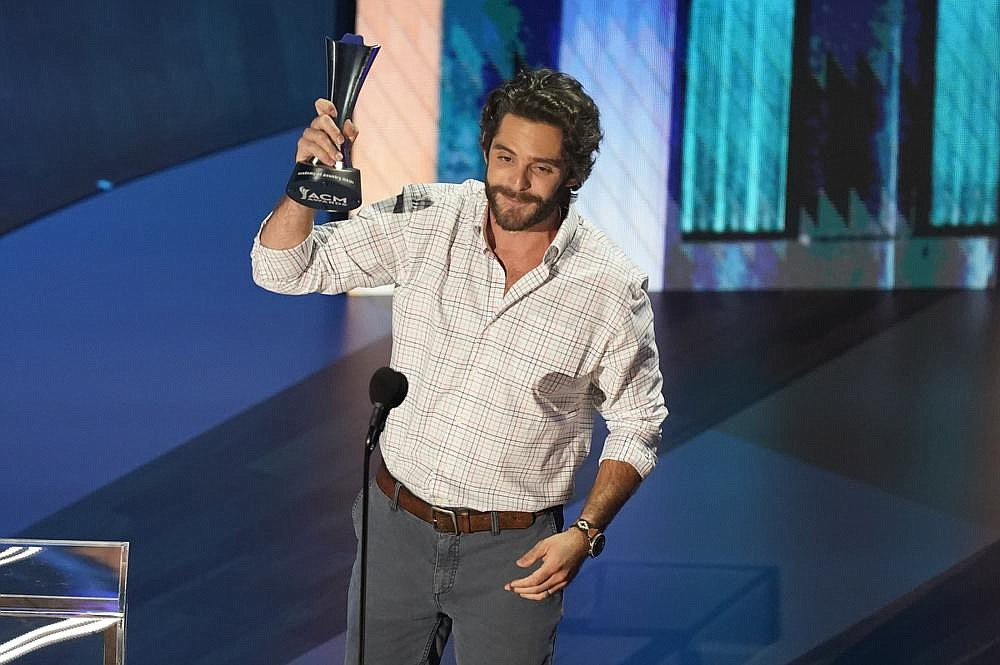 Thomas Rhett accepts the entertainer of the year award in a tie with Carrie Underwood during the 55th annual Academy of Country Music Awards on Wednesday at the Grand Ole Opry House in Nashville.