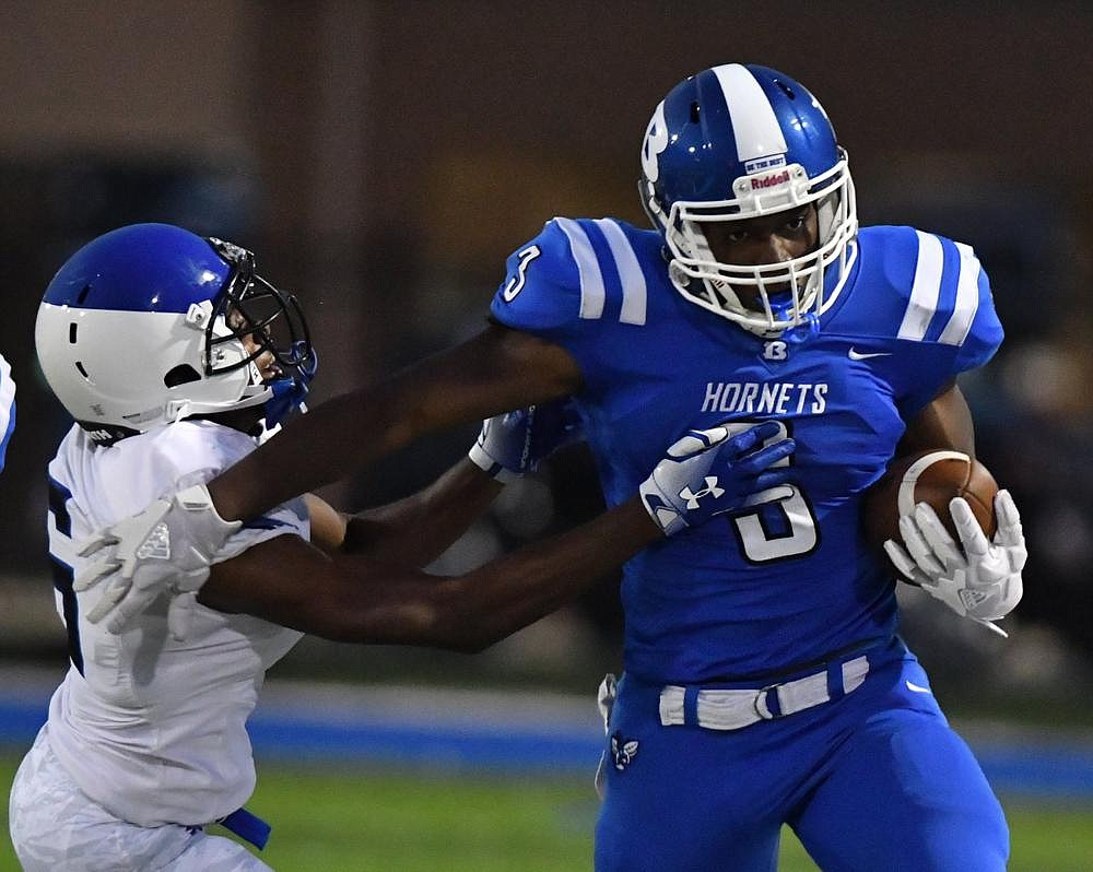 Bryant running back Jamarien Bracy (right) gets past Cedar Hill (Texas) Trinity Christian defensive back Cameron Wilson during Friday night's game at Bryant. More photos available at arkansasonline.com/919trinity. (Special to the Democrat-Gazette/Jimmy Jones)