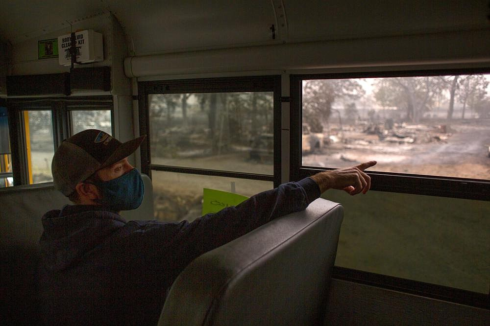 Stuart Warren, a town councilman, points out a house he once lived in that burned, in Phoenix, Ore., a town devastated the previous week by the Almeda Fire. (The New York Times/Alisha Jucevic)