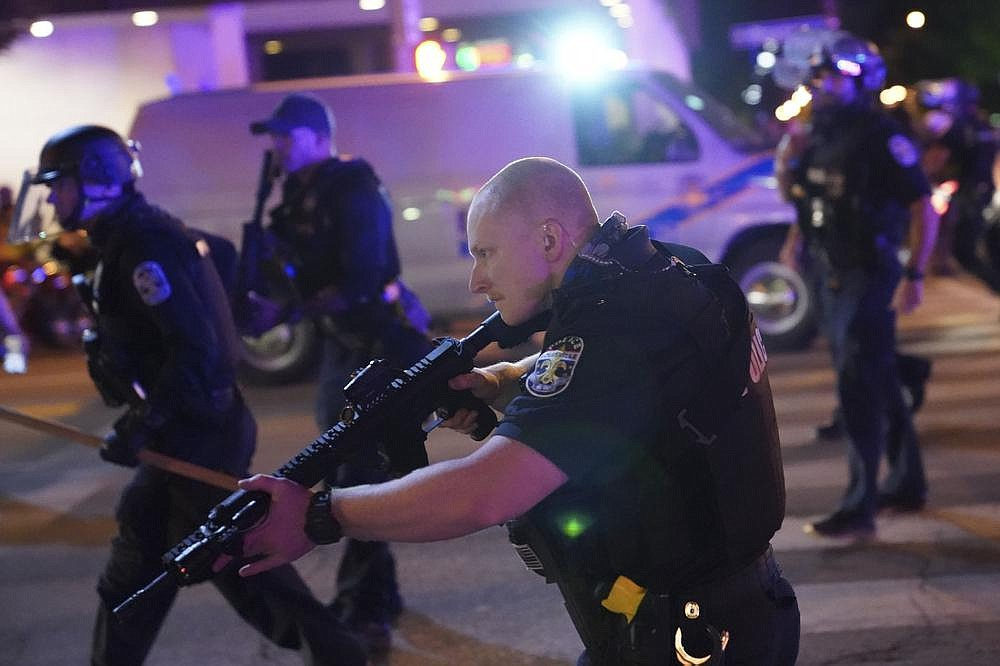 Louisville, Ky., police fan out Wednesday night after officers were shot. Gov. Andy Beshear, a Democrat, said he authorized a limited deployment of the National Guard after a grand jury released its indictment related to the Breonna Taylor shooting investigation. (AP/John Minchillo)