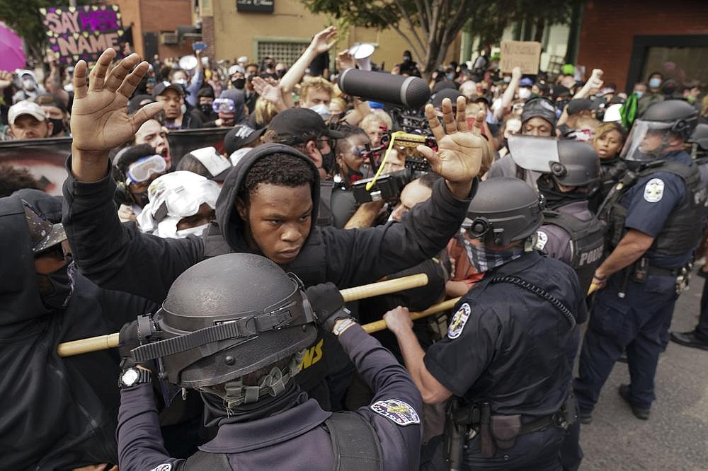 Police officers and protesters converge during a demonstration Wednesday in Louisville, Ky. Protests turned violent later in the day, and two officers were wounded in a shooting. (AP/John Minchillo)