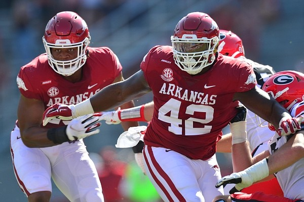 Arkansas defensive linemen Julius Coates (left) and Jonathan Marshall (right) look to make a play in the backfield in the Razorbacks' season opener against Georgia on Sept. 26, 2020 in Fayetteville.