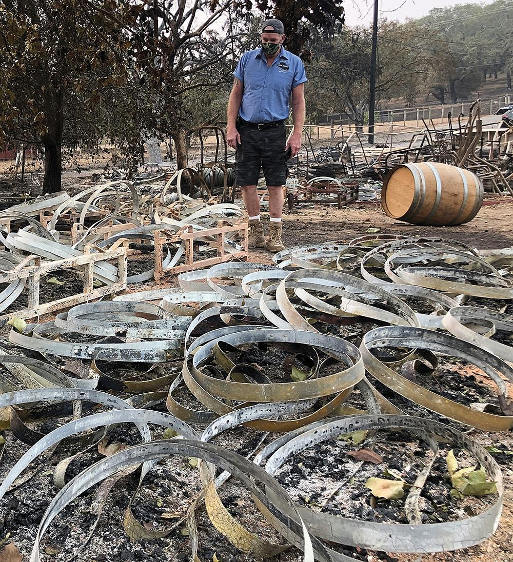 Kevin Conant stands Wednesday amid hundreds of metal rings left from wine barrels that were destroyed when a wildfire swept over his business, Conants Wine Barrel Creations, in Santa Rosa, Calif. Conant and his family escaped with little more than the clothes on their backs. Flames devoured swaths of brush and trees in Northern California on Wednesday as the weather remained hot and dry. More photos at arkansasonline.com/101fires/. Video at arkansasonline.com/101napa/.