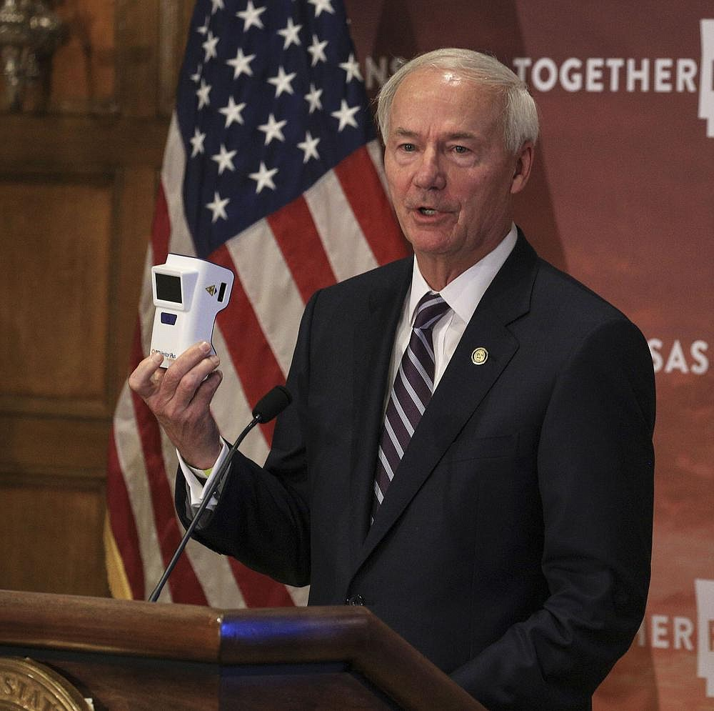 Gov. Asa Hutchinson holds an antigen testing machine Tuesday Sept. 15, 2020 in Little Rock as he speaks during a covid-19 briefing at the state Capitol. 