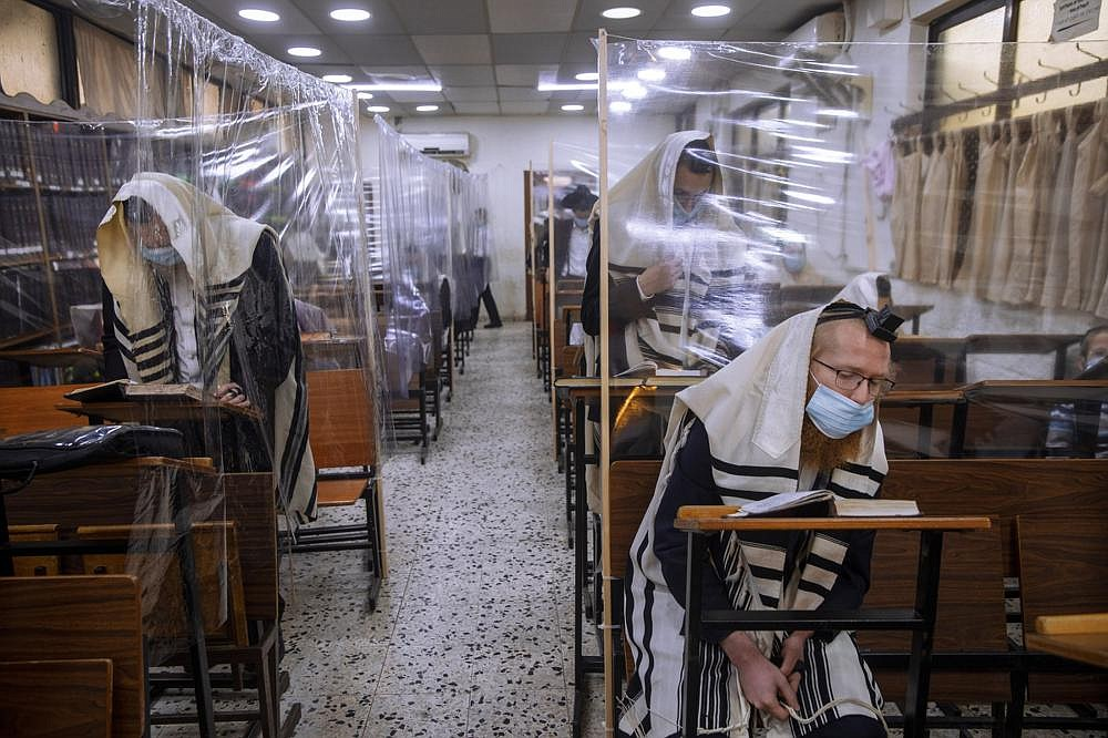 Social distancing and the wearing of face masks are among the measures Ultra-Orthodox Jews are taking during a morning prayer next to their houses, as synagogues are limited to 20 people due to the coronavirus pandemic, in Bnei Brak, Israel. (AP/Oded Balilty)