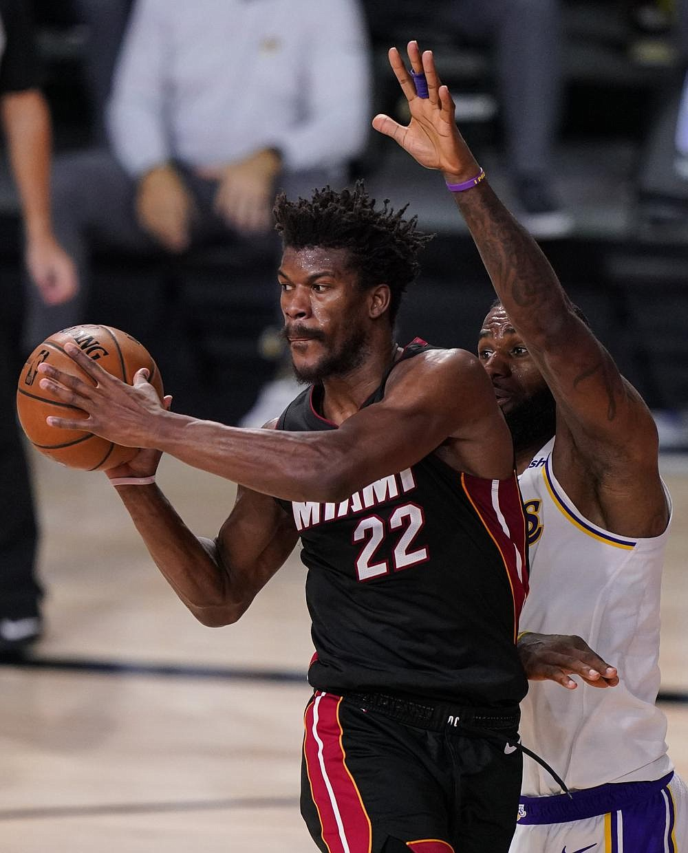Miami Heat guard Jimmy Butler makes a pass as LeBron James of the Los Angeles Lakers defends during the second half of Game 3 of the NBA Finals on Sunday in Lake Buena Vista, Fla. Butler had 40 points, 11 rebounds and 13 assists as the Heat beat the Lakers 115-104 to get within 2-1 in the series. (AP/Mark J. Terrill)