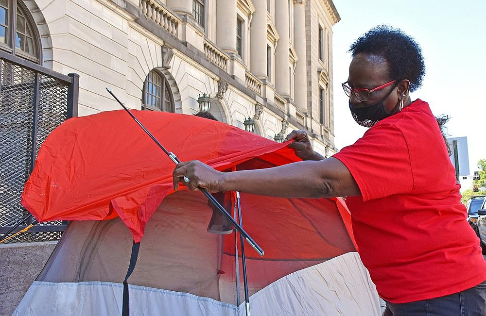 Bobbie Taylor, an organizer for Arkansas Community Organizations, puts up a tent Thursday outside the Pulaski County Courthouse in Little Rock during a protest against evictions. (Arkansas Democrat-Gazette/Staci Vandagriff)