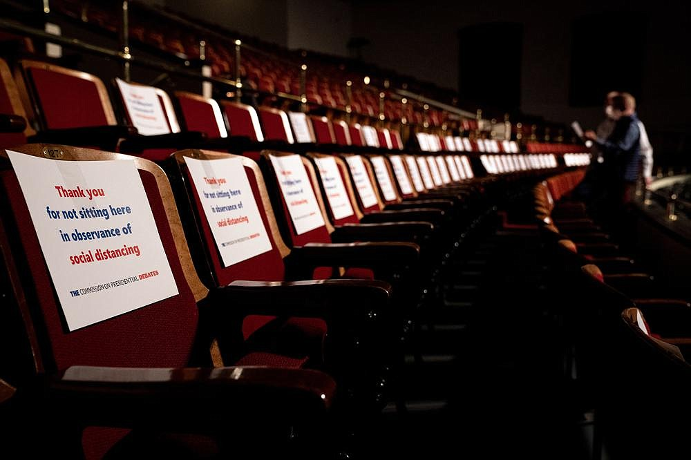 Workers place social-distancing signs on seats Wednesday at the University of Utah in Salt Lake City for the vice presidential debate. Donors and other guests sat in the seats, though there were at least two empty seats between people. (The New York Times/Erin Schaff)
