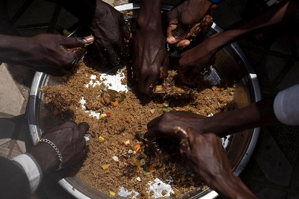 Pilgrims from the Mouride Brotherhood share a large dish of traditional Senegalese food distributed by volunteers in front of the Touba Grand Mosque on Tuesday.  You were among the tens of thousands of people who gathered for the Order's annual Great Magal Pilgrimage this week.  (AP / Leo Correa)