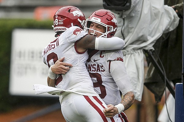 Arkansas quarterback Feleipe Franks (13) celebrates with wide receiver Mike Woods (8) after a touchdown against Auburn during the second quarter of an NCAA college football game on Saturday, Oct. 10, 2020, in Auburn, Alabama. (AP Photo/Butch Dill)