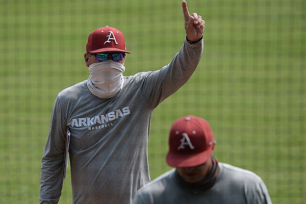 Arkansas coach Dave Van Horn gestures Friday, Sept. 18, 2020, to a friend in the stands during practice at Baum-Walker Stadium in Fayetteville.