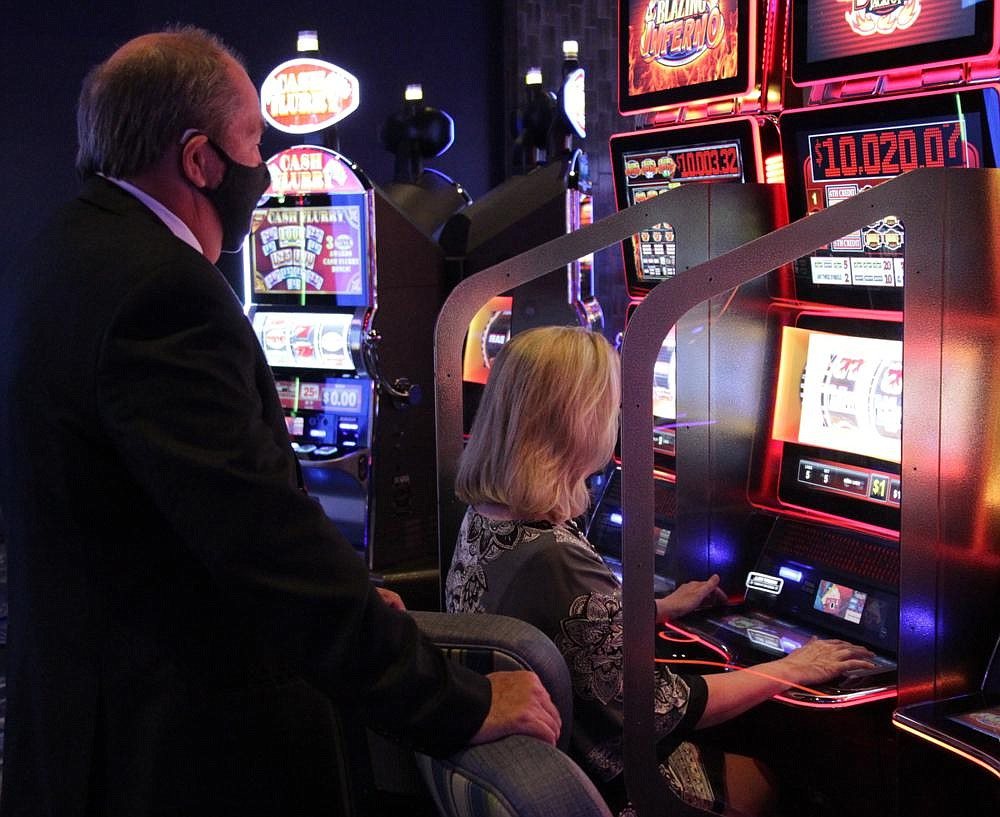 """Prosecuting Attorney Kyle Hunter watches as his wife, Tina, racks up points on one of the new progressive slot machines at Saracen Casino. When the photo was taken, Tina Hunter was up to around $1,250 on the machine. """"She started out with $100,"""" Kyle said. """"If she hits the double jackpot, we're out of here.""""  (Pine Bluff Commercial/Dale Ellis)"""