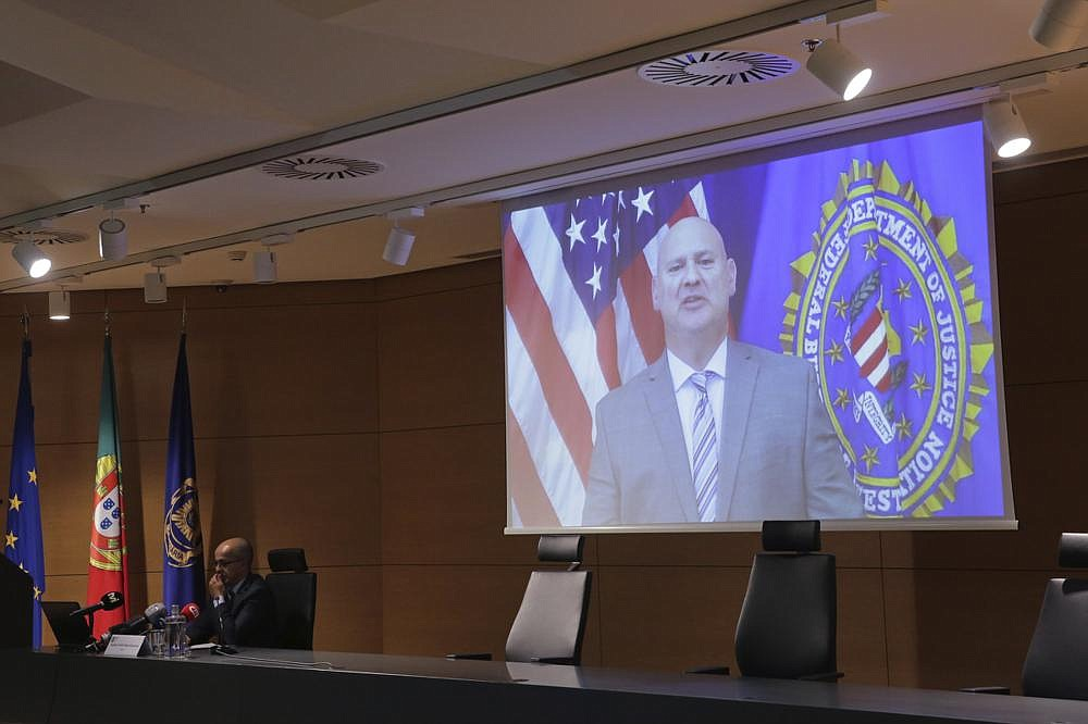 Pittsburgh FBI Special Agent Michael Christman speaks Thursday in a video presented by Portuguese police chief inspector Paulo Goncalves (left) during a news conference at police headquarters in Lisbon. (AP/Armando Franca)
