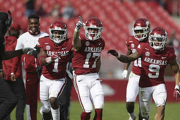 Arkansas defensive backs Hudson Clark (17), Jalen Catalon (1) and Greg Brooks (9) celebrate after Clark intercepted a pass during a game against Ole Miss on Saturday, Oct. 17, 2020, in Fayetteville. All three players had at least one interception and the Razorbacks intercepted six passes in their 33-21 victory over the Rebels.