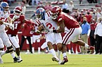Arkansas defensive lineman Julius Coates (13) tackles Mississippi quarterback Matt Corral (2) for a loss during the first half of an NCAA college football game Saturday, Oct. 17, 2020, in Fayetteville, Ark. (AP Photo/Michael Woods)