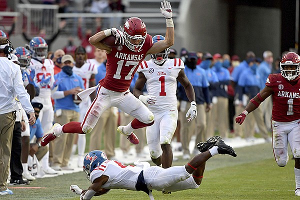 Arkansas defensive back Hudson Clark (17) leaps over Ole Miss running back Tylan Knight (4) as he returns an interception during the second half of an NCAA college football game Saturday, Oct. 17, 2020, in Fayetteville. (AP Photo/Michael Woods)