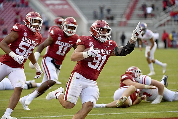 Arkansas linebacker Grant Morgan (31) celebrates as he returns an interception for a touchdown against Ole Miss during the second half of an NCAA college football game Saturday, Oct. 17, 2020, in Fayetteville. (AP Photo/Michael Woods)
