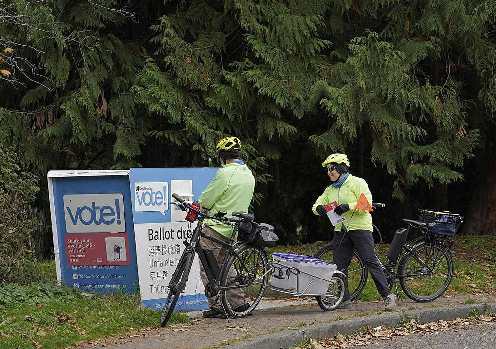 Two people out for a bike ride put their ballots in an outdoor drop box Friday near Gas Works Park in Seattle. Washington is a vote-by-mail state, but ballots also can be deposited at drop boxes, which opened this week in the Seattle area. (AP/Ted S. Warren)