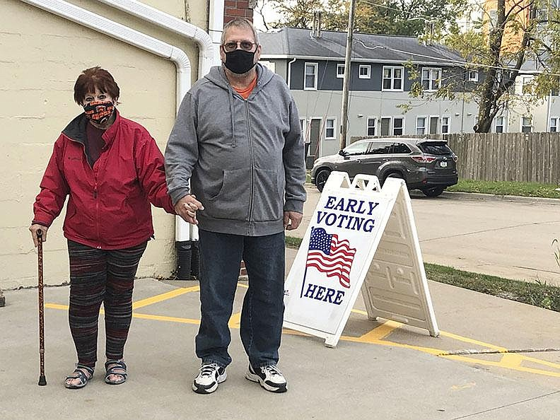 Tim and Pat Tompkins arrive to vote early Friday in Bettendorf, Iowa. The couple said they were concerned about coronavirus exposure in bigger crowds but were determined to vote, and carried their own hand sanitizer. (AP/Geoff Mulvihill)