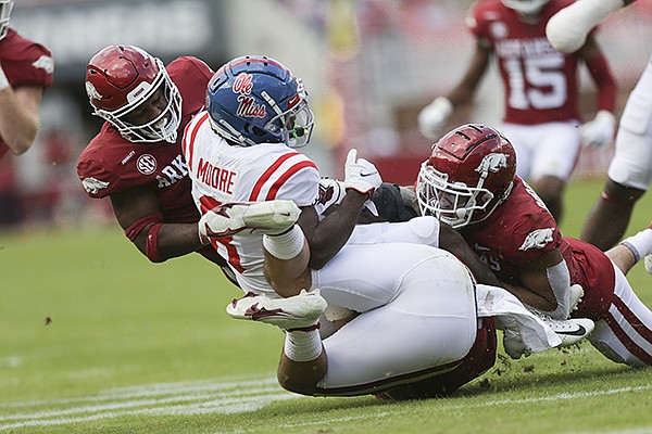 Arkansas players tackle Ole Miss receiver Elijah Moore during a game Saturday, Oct. 17, 2020, in Fayetteville.