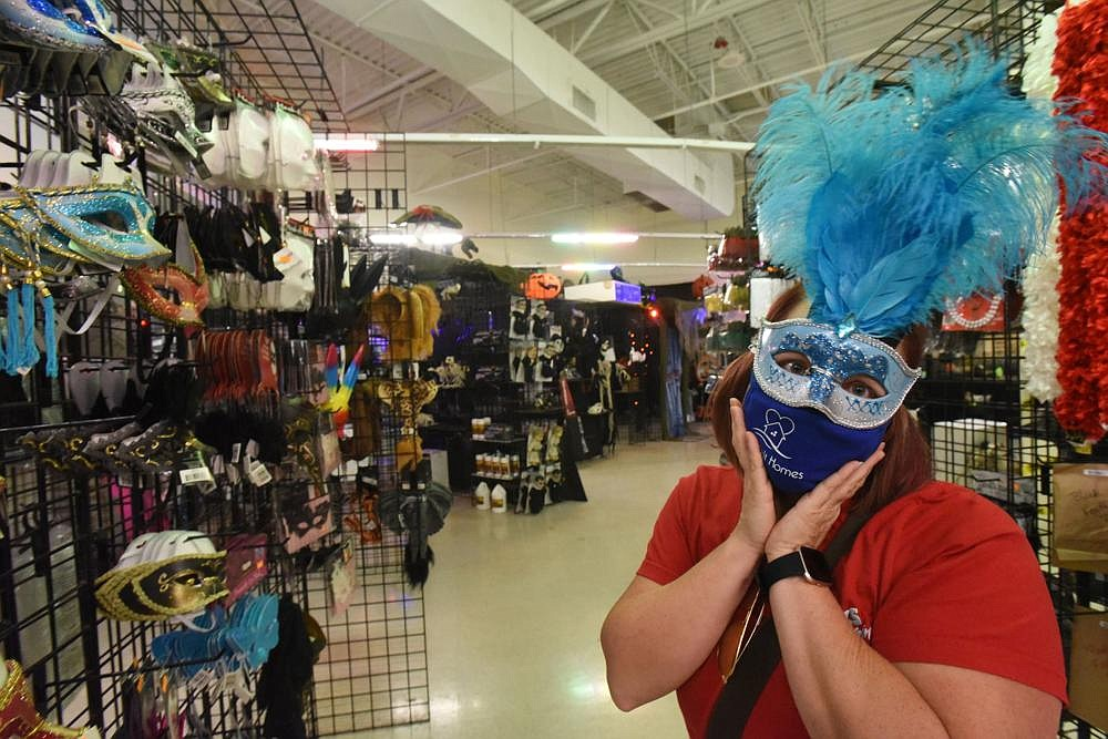 Amber Green of Bentonville tries on a costume mask last week at Halloween Express at Frisco Station Mall in Rogers.