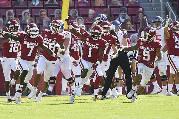 Arkansas defensive players Joe Foucha (7), Jalen Catalon (1), Hudson Clark (17) and Greg Brooks (9) celebrate after an Ole Miss turnover during an NCAA college football game Saturday, Oct. 17, 2020, in Fayetteville. (AP Photo/Michael Woods)