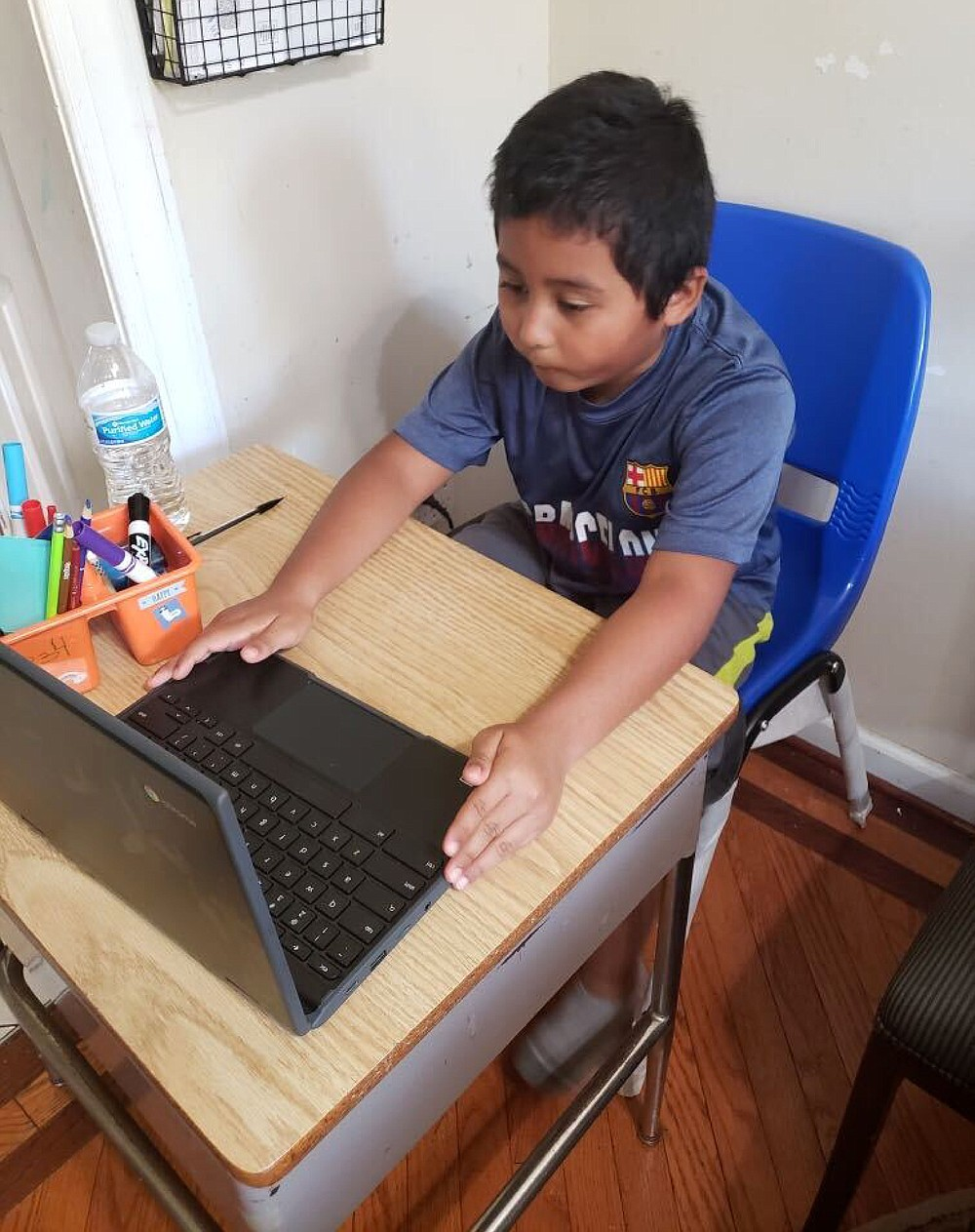 In this photo provided by Jessica Berrellez, student Jordan Dominguez Garcia attends a virtual class using his new desk, which was donated by the community, Thursday, Oct. 8, 2020, in Gaithersburg, Maryland. (Jessica Berrellez via AP)
