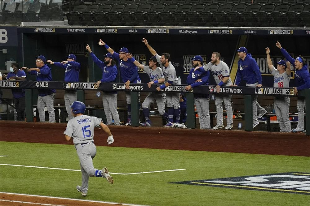 Los Angeles catcher Austin Barnes (15) rounds the bases Friday as teammates cheer his home run during the sixth inning of the Dodgers' 6-2 victory over the Tampa Bay Rays in Game 3 of the World Series at Globe Life Field in Arlington, Texas. (AP/Tony Gutierrez)