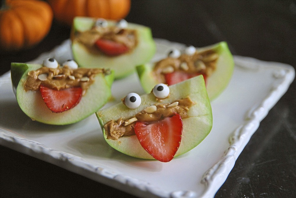 Turn apple wedges into spooky, silly and healthful apple monsters with almond teeth and sliced strawberry eyes. (TNS/Pittsburgh Post-Gazette/Gretchen McKay)