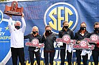 Arkansas coach Lance Harter (left) holds up the SEC championship trophy as he celebrates with his runners following the SEC Cross Country Championships on Friday, Oct. 30, 2020, in Baton Rouge, La.