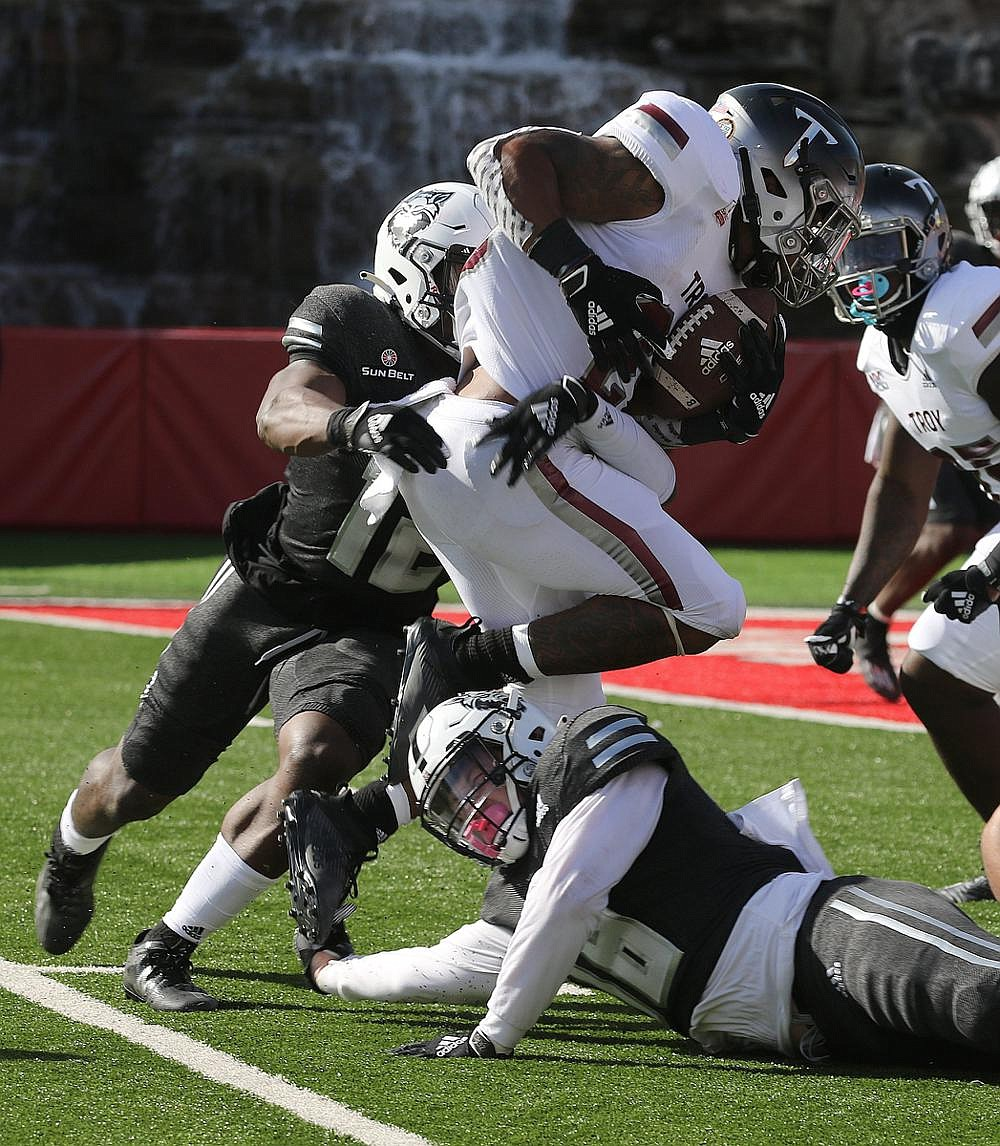 Troy running back B.J. Smith (center) is tackled for a loss by Arkansas State linebackers CJ Harris (left) and Justin Rice during the Red Wolves' 38-10 loss Saturday. Rice, who had 14 tackles, is among players ASU is counting on to help the Red Wolves make improvements on defense.